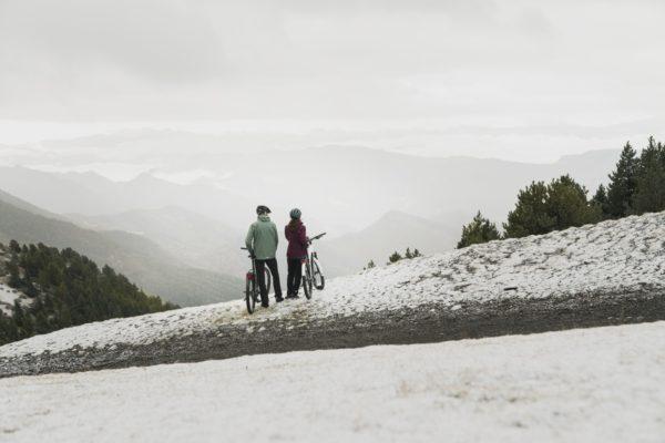 Et par på elsykkeltur på sine Kalkhoff Entice elsykler. Syklistene er nesten på toppen av en bakke. Det ligger snø på bakken.